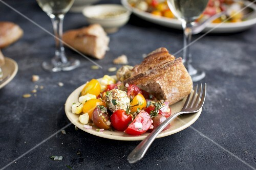 Cherry tomato salad and goats' cheese balls with toasted seeds
