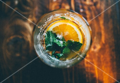 A cocktail garnished with a slice of orange and mint