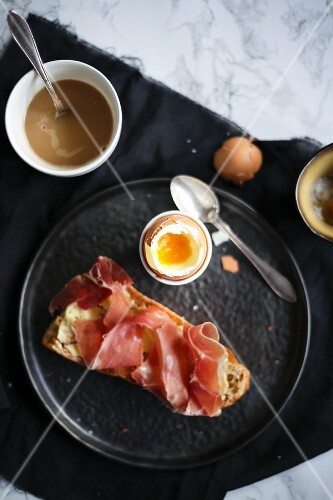 Breakfast with a soft-boiled egg and bread with ham