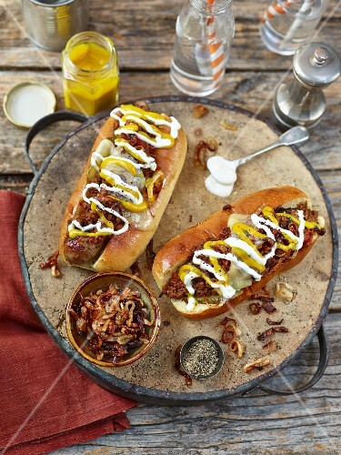 Chilli hot dogs topped with fried onion, mustard and mayonaise