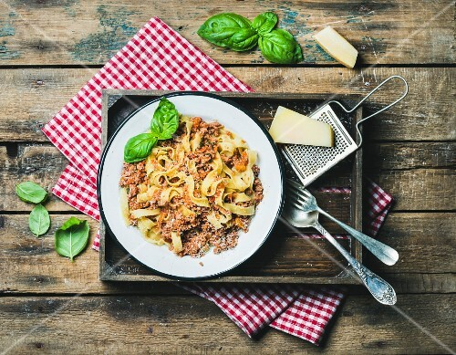 Tagliatelle Bolognese with Parmesan cheese and fresh basil in wooden tray over rustic wooden background