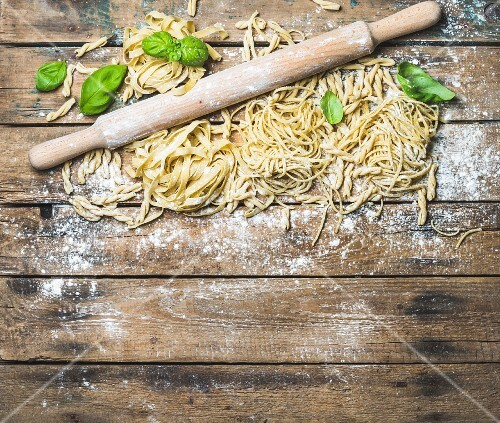 Various homemade fresh uncooked Italian pasta with flour, green basil leaves and plunger on shabby background