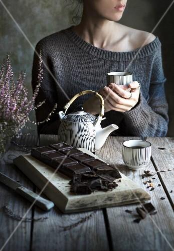 Frau trinkt Tee, im Vordergrund dunkle Schokolade