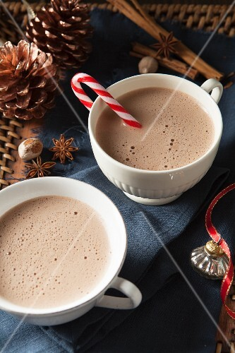 Two large white mugs of frothy hot chocolate (one with a candy cane) for Christmas
