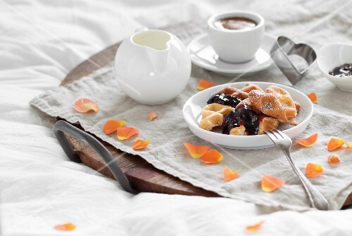 Quark waffles with jam and icing sugar on a breakfast tray