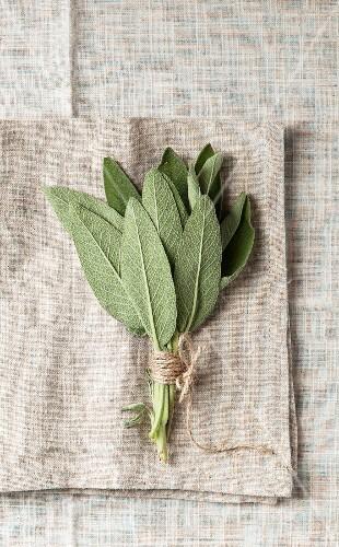 A bundle of sage on a grey, coarse linen napkin