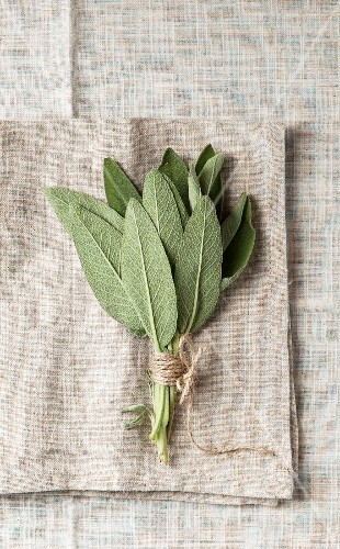 A bundle of sage on a grey, coarse linen napkin