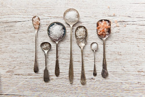Seven vintage spoons of diffrent types of salt on a white wooden surface