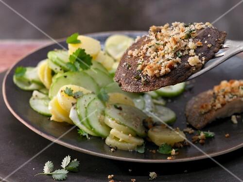 Grilled portobello mushroom schnitzel with a cucumber and potato salad