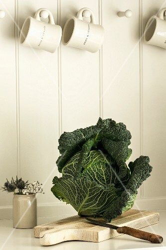 Savoy cabbage on a chopping board in a kitchen