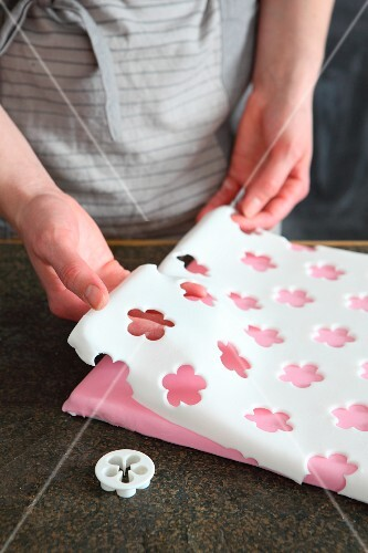 A sheet of fondant icing with cut-out flowers for a cake board
