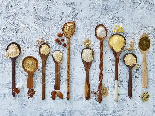 Various types of flour on wooden spoons (seen from above)