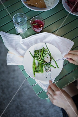Woman eating blanched green asparagus (overhead view)