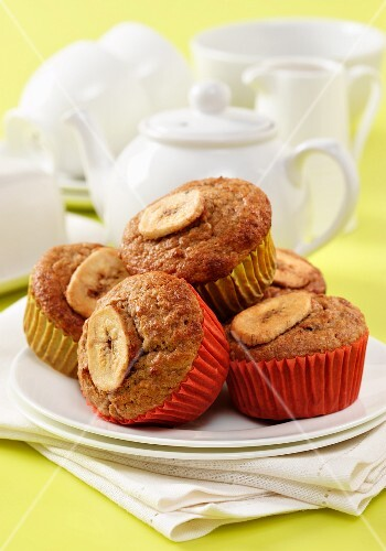 Muesli and banana muffins on a white plate with napkins and a white teaset in background sitting on a yellow surface