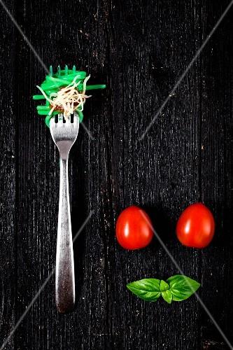 Grüne Pasta mit Tomaten und Basilikum auf Gabel auf schwarzem Holzbrett