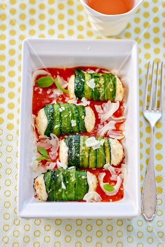 Zucchini rolls with fresh cheese filling on tomato sauce