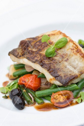 Pan fried fish on a bed of vegetables