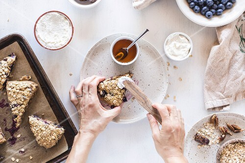 A woman is spreading ricotta cheese on scones with blueberries and lemon