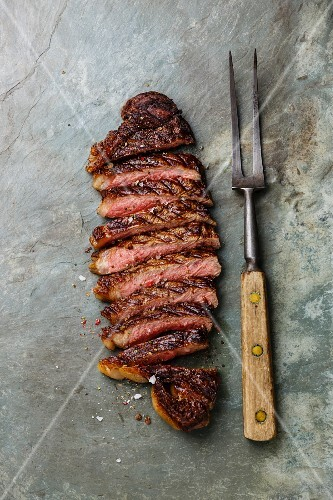 Sliced grilled beef barbecue Striploin steak and meat fork on gray stone slate background
