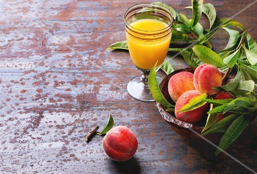 Peaches on branch with leaves in wooden bowl and glass with peach s juice over old metal background