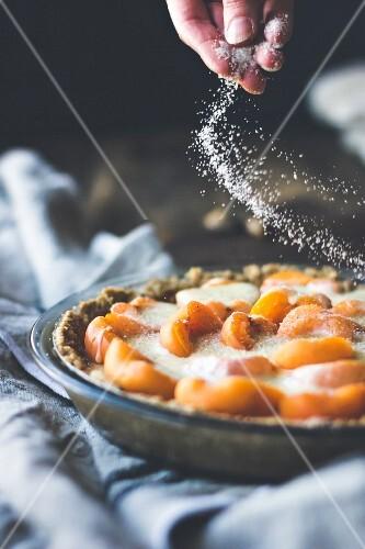 Aprikosentarte mit Custard Cream wird mit Zucker bestreut