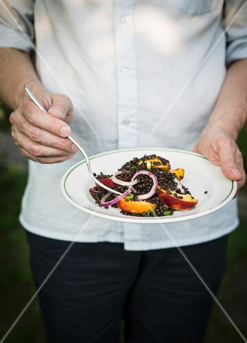Man holding a plate with lentil and fruit salad