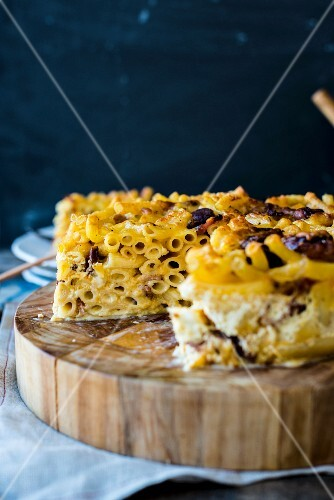 Slices of macaroni cheese cake on a wooden board