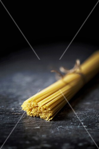 A bunch of uncooked spaghetti on a dark background