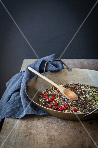 Whole spices prepared for roasting in a pan on wooden table