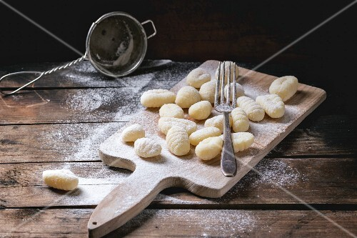 Uncooked homemade potato gnocchi with fork and strainer on vintage cutting board over wooden table with flour