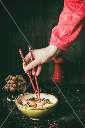 Female hand in red shirt take by chopsticks noodles from asian ramen soup with shrimp, onion, sliced egg and mushrooms