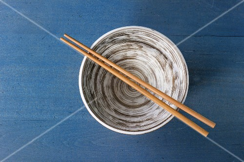 Empty ceramic bowl with bamboo chopsticks over blue wooden surface
