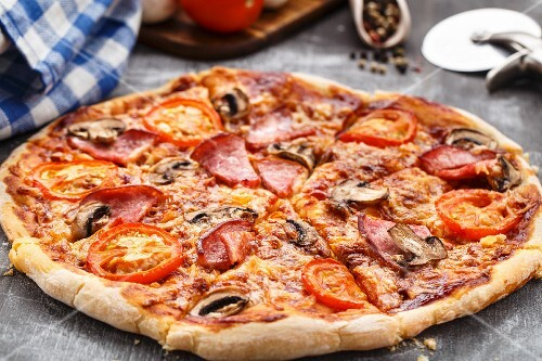 Pizza with tomatoes, ham and mushrooms on a table