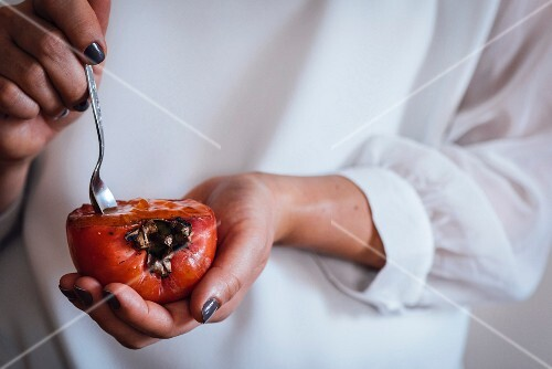 Woman dipping spoon into a persimmon cup