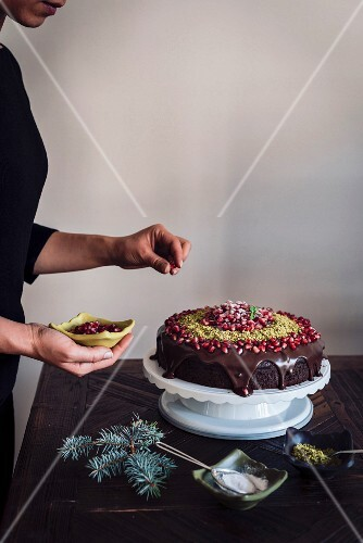 A woman decorating a Christmas Chocolate Cake with pomegranate seeds