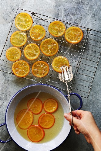 Female hand placing a slice of candied orange on a grill to dry
