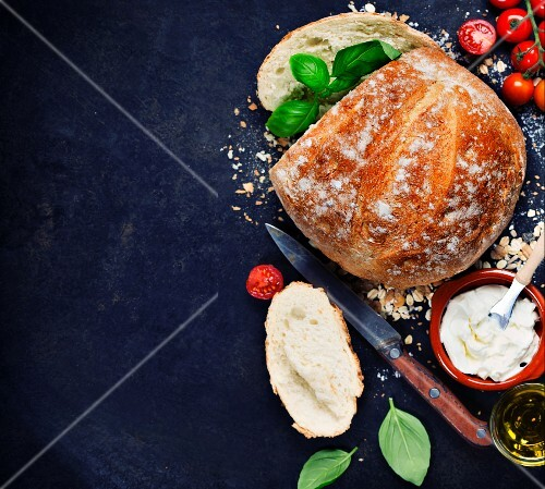 Homemade bread loaf and fresh ingredients for making sandwiches (tomatoes, basil, olive oil, cream cheese)