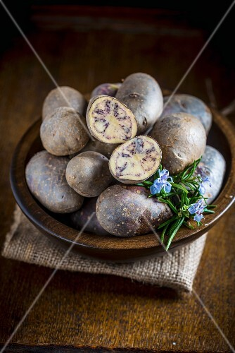Purple potatoes in a wooden bowl, with one cut open