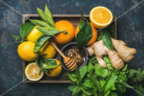 Ingredients for making immunity boosting natural drink: Lemons, oranges, mint, ginger, honey in wooden box