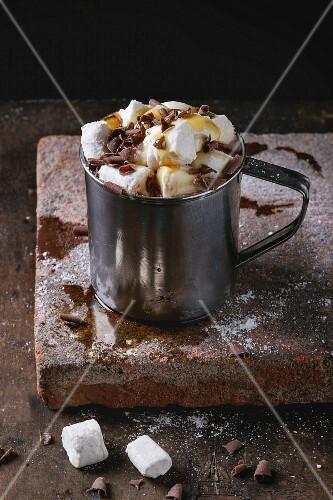 Heiße Schokolade mit Marshmallows, Schokoraspeln und Sirup in Metallbecher