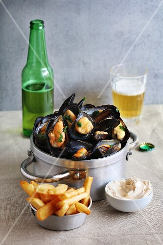 Cooked mussels in an aluminum pan with french fries, mayonnaise and a glass of beer