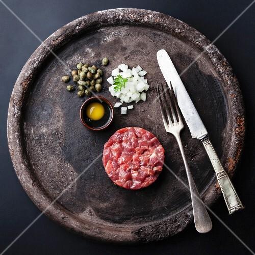 Beef Tartar mit Ei, Kapern und frischen Zwiebeln auf schwarzer Platte