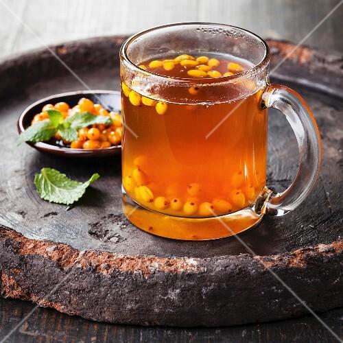 Tea with sea buckthorn on dark background