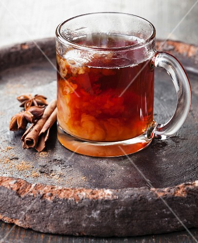 Hot tea with milk and spices on dark background