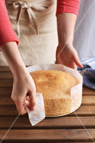 Female hands peeling the parchment paper from the sides of the sponge cake