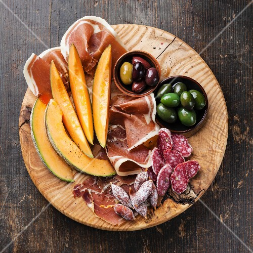 Antipasto ham, melon and olives on wooden background