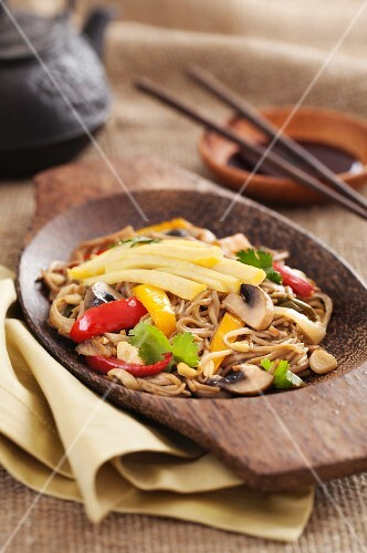 Asian yakisoba noodle with fried vegetables and omelette on a wooden plate