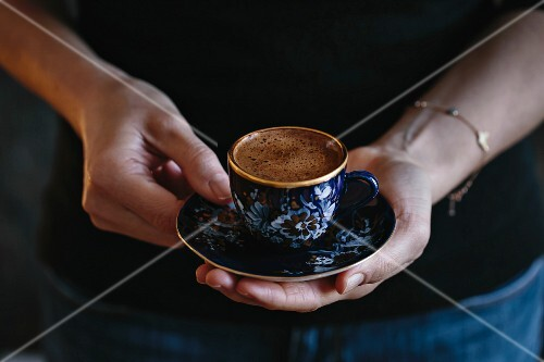 A woman is holding a cup of Turkish coffee with foam on top (with both hands)