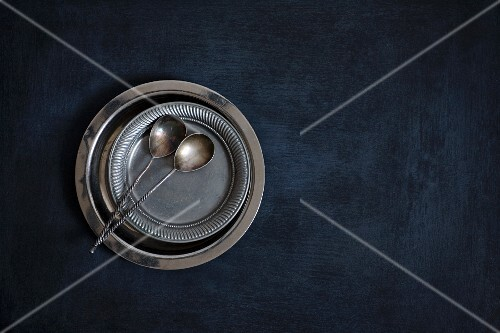 Metal plates and vintage silver spoons on a black background