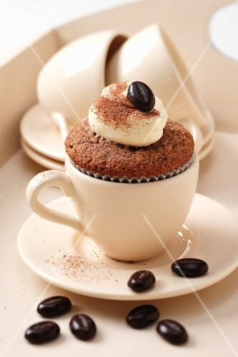 Cappuccino flavoured cupcakes with coffee cups and chocolate coffee beans on a cream coloured tray